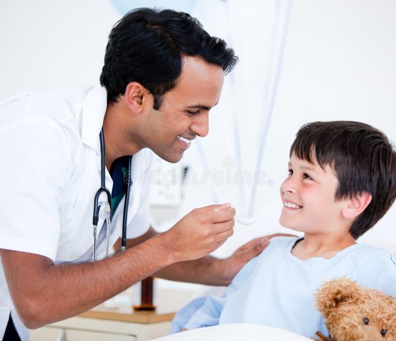 Ragazzino ammalato sorridente che cattura medicina immagini stock libere da diritti