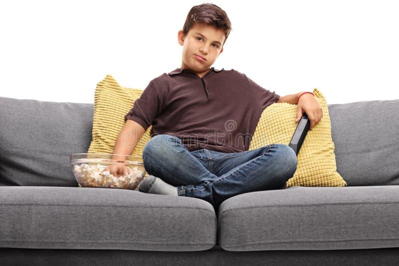 Ragazzino annoiato che guarda TV immagine stock