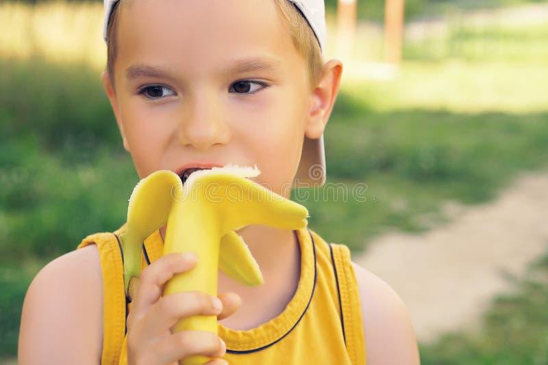 Ragazzino in buona salute che mangia il fondo della natura del bananaon Il bambino felice gode di di mangiare la frutta fresca fotografia stock