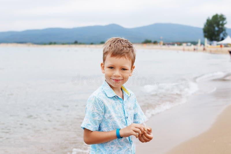 Ragazzino in camicia e shorts sulla sabbia della spiaggia Hav del ragazzino immagine stock