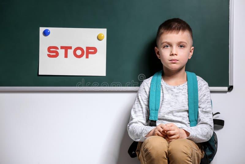 Ragazzino che è oppresso alla scuola vicino alla lavagna fotografia stock libera da diritti