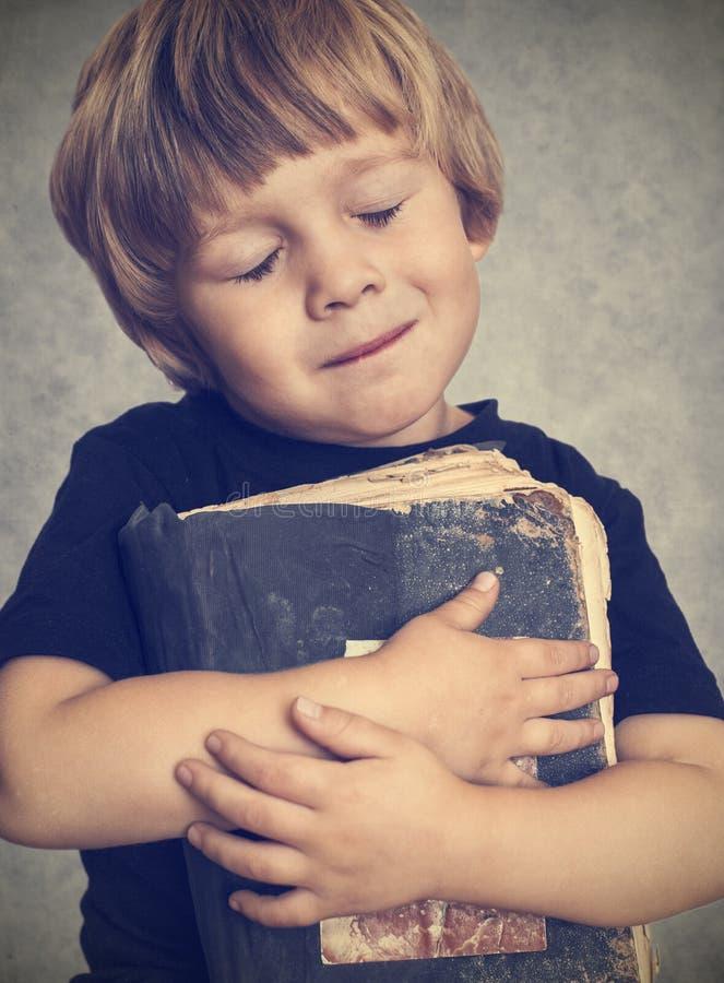 Ragazzino che abbraccia un vecchio libro immagine stock libera da diritti