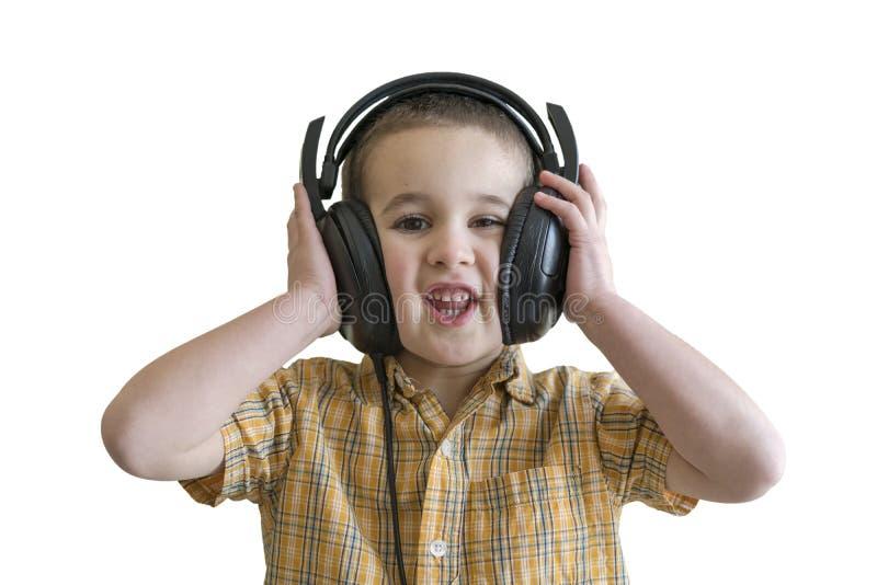 Ragazzino che ascolta la musica in grandi cuffie nere Isolato su priorità bassa bianca fotografie stock