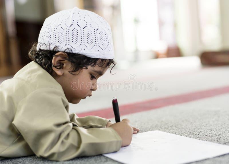 Ragazzino che assorbe allegro una moschea durante il Ramadan fotografia stock