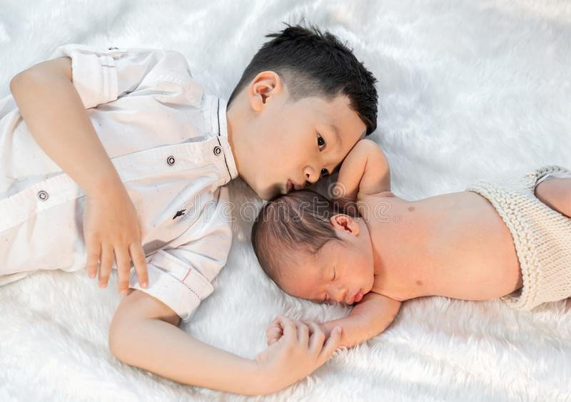 Ragazzino che bacia suo fratello del neonato sul letto immagini stock libere da diritti