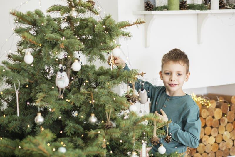 Ragazzino che decora l'albero di Natale con i giocattoli e le palle Bambino sveglio che prepara a casa per la celebrazione di nat immagini stock