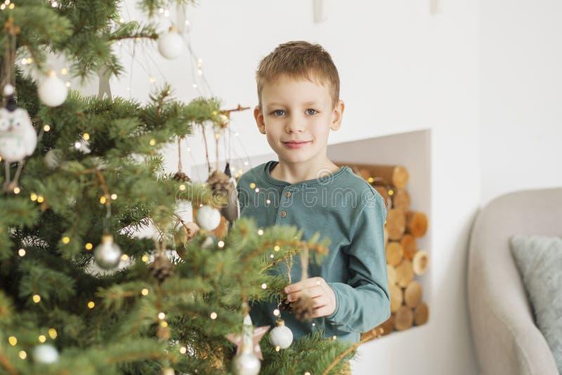 Ragazzino che decora l'albero di Natale con i giocattoli e le palle fotografia stock