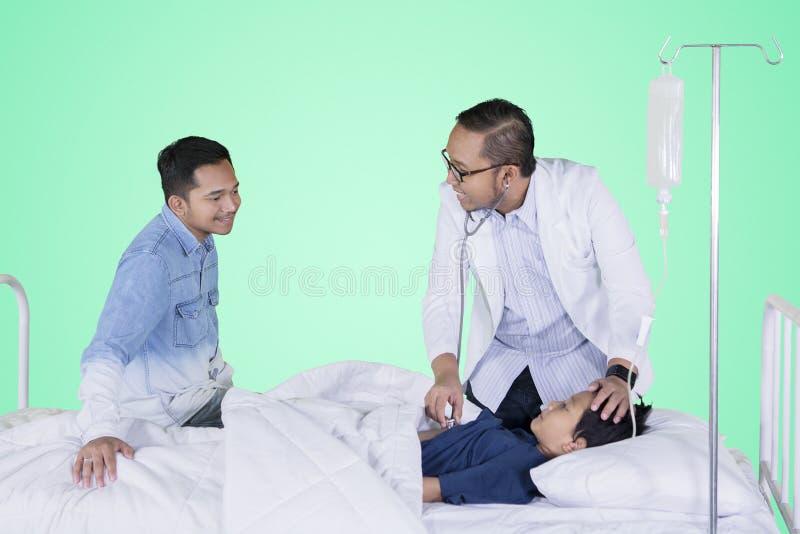 Ragazzino che esamina dal suo medico nello studio immagine stock