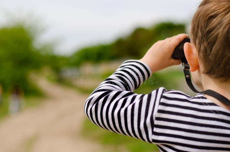 Ragazzino che esplora il legno con il binocolo immagine stock