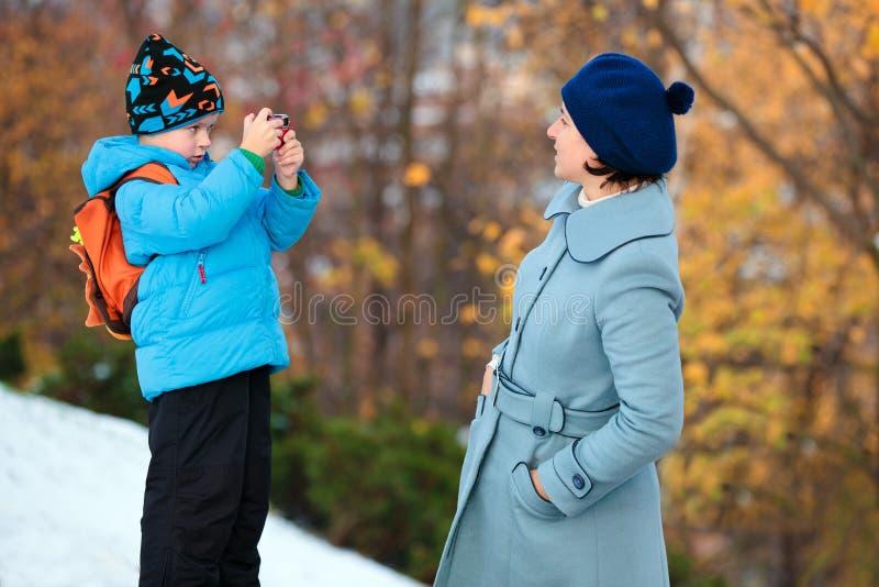 Ragazzino che fotografa la sua madre alla sosta di autunno immagini stock