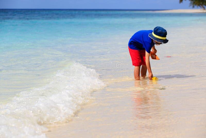 Ragazzino che gioca con la barca di carta alla spiaggia fotografia stock libera da diritti