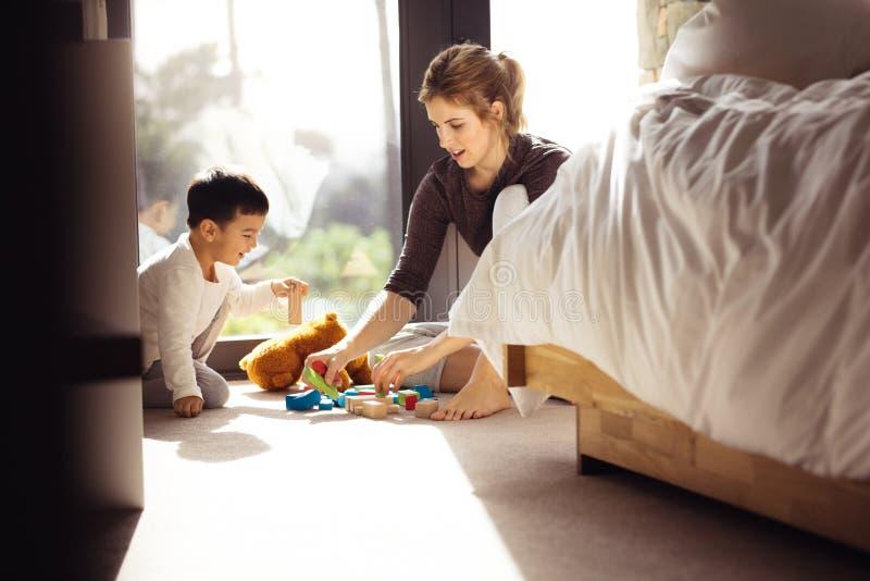 Ragazzino che gioca i giocattoli con sua madre a casa fotografie stock libere da diritti