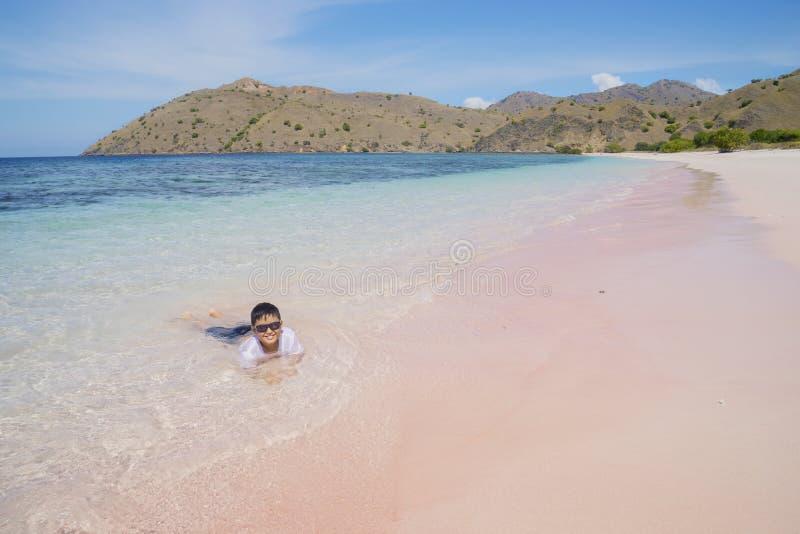 Ragazzino che gioca onda sulla spiaggia rosa immagine stock libera da diritti