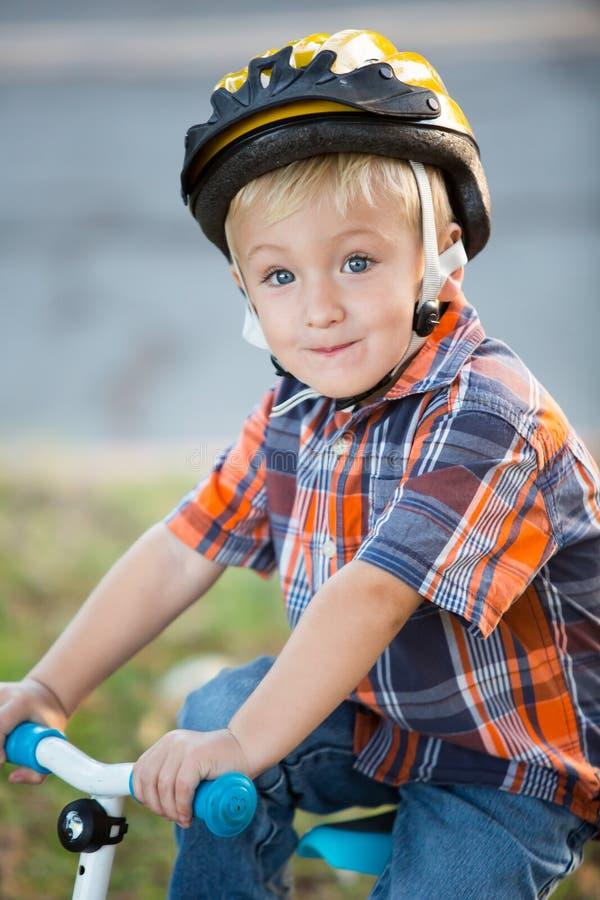 Ragazzino che guida la sua bici che indossa un casco immagine stock libera da diritti