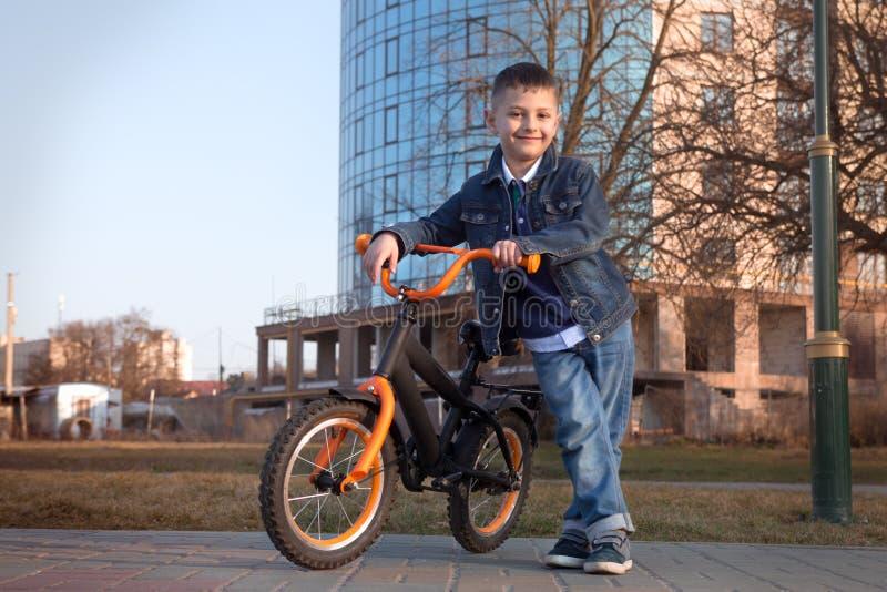 Ragazzino che guida la sua bici nel parco della città fotografia stock