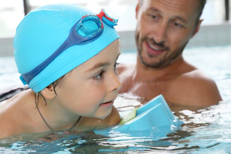 Ragazzino che impara nuotare con il monitor fotografia stock