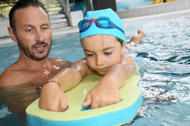 Ragazzino che impara nuoto con il monitor fotografia stock