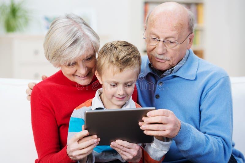 Ragazzino che legge una compressa con i suoi nonni immagini stock