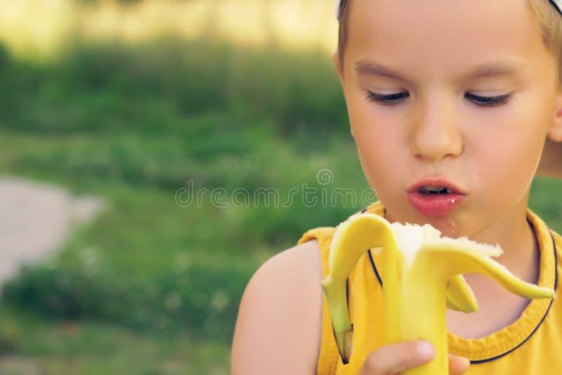 Ragazzino che mangia banana, esaminante macchina fotografica con il fronte felice, mostrante i pollici su Il bambino felice gode  immagine stock