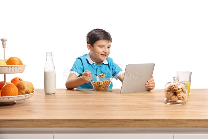 Ragazzino che mangia i cereali per brekfast ad un contatore di legno e che guarda in una compressa immagini stock