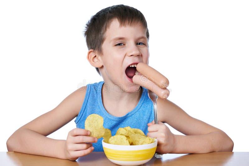 Ragazzino che mangia le salsiccie e le patatine fritte isolate fotografia stock