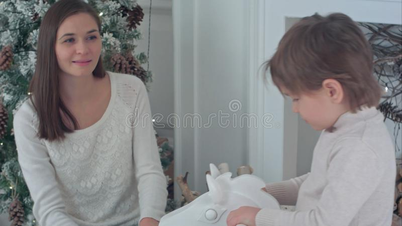 Ragazzino che monta cavallo a dondolo di legno, mentre madre felice che lo guarda sedersi vicino all'albero di Natale fotografie stock libere da diritti