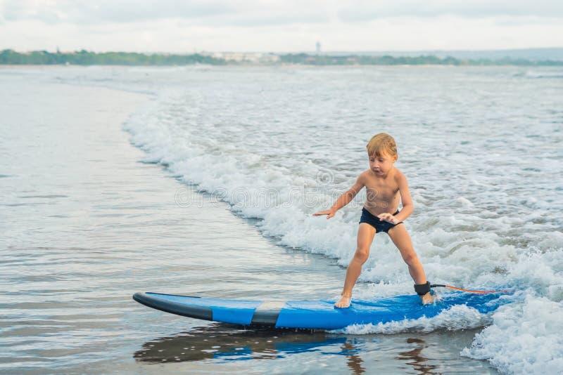 Ragazzino che pratica il surfing sulla spiaggia tropicale Bambino sul bordo di spuma sull'onda di oceano Sport acquatici attivi p fotografia stock libera da diritti