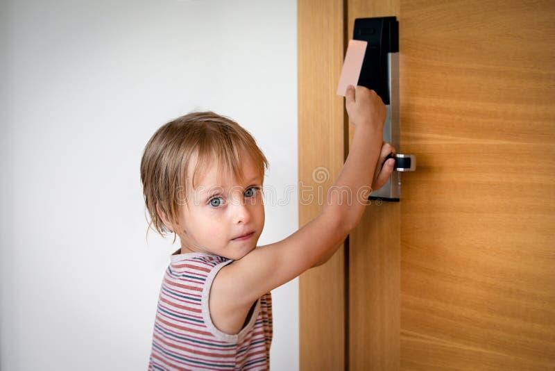 Ragazzino che prova alle porte aperte con la serratura della carta all'hotel fotografie stock libere da diritti