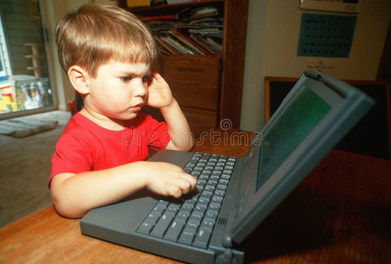 Ragazzino che prova a lavorare al computer portatile immagini stock