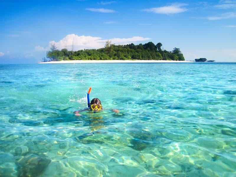 Ragazzino che si immerge accanto all'isola tropicale fotografia stock