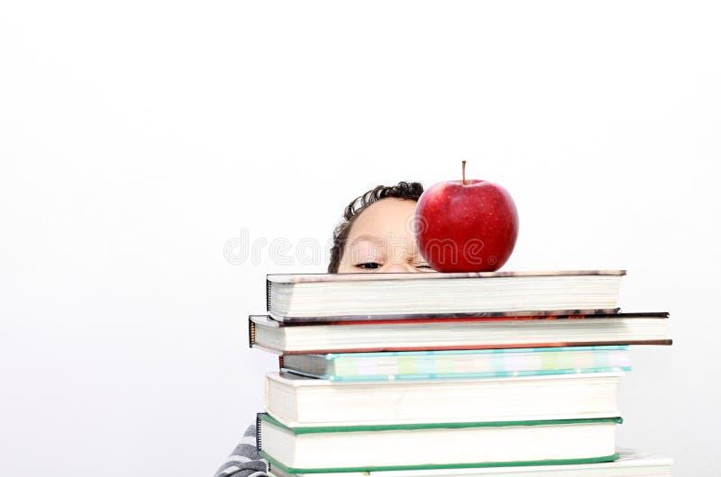 Ragazzino che si nasconde dietro una grande pila di libri fotografia stock