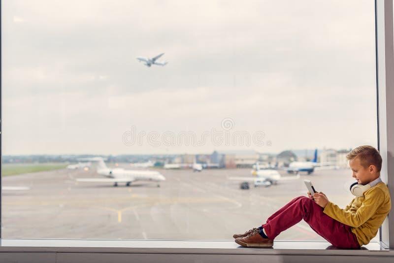 Ragazzino che si siede all'aeroporto fotografia stock