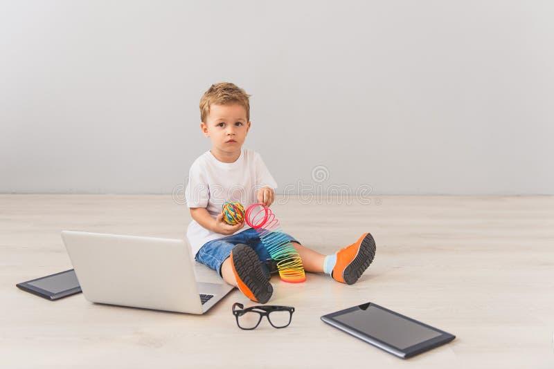 Ragazzino che si siede con gli aggeggi digitali in studio fotografia stock libera da diritti