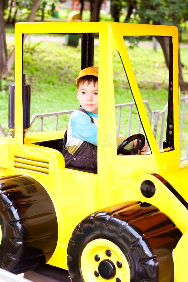 Ragazzino che sorride e che gioca nell'automobile del giocattolo immagine stock libera da diritti