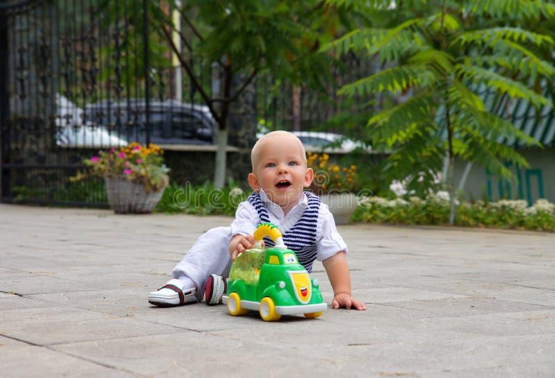 Ragazzino che sorride e che gioca nell'automobile del giocattolo fotografie stock libere da diritti