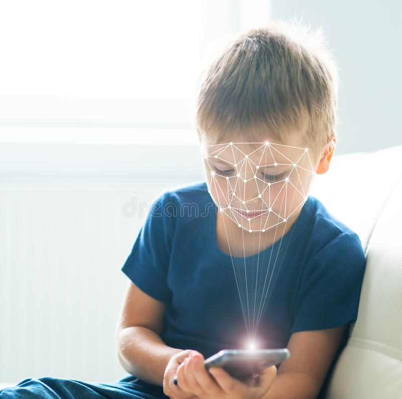 Ragazzino che usando autenticazione di identificazione del fronte Bambino con uno smartphone Concetto indigeno dei bambini di Dig fotografia stock