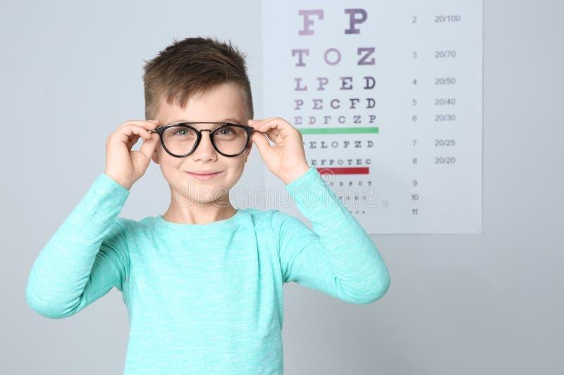 Ragazzino con i vetri che visita il medico dei bambini in clinica immagine stock libera da diritti
