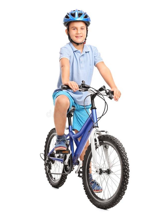 Ragazzino con il casco blu che si siede sulla sua bicicletta fotografia stock libera da diritti