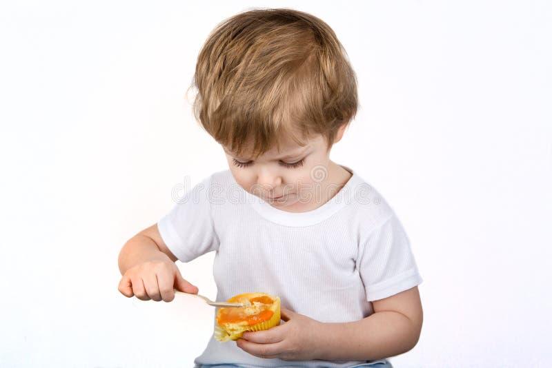 Ragazzino con il cibo della focaccina della torta di formaggio. fotografia stock libera da diritti