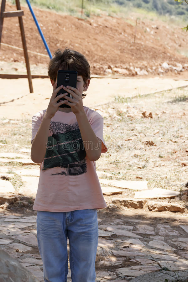 Ragazzino con il dispositivo mobile fotografia stock libera da diritti