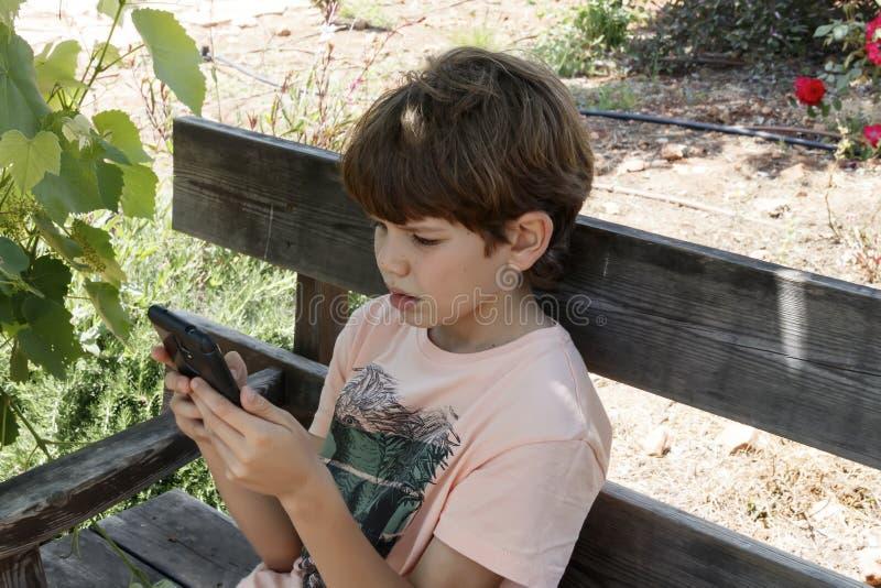 Ragazzino con il dispositivo mobile immagine stock