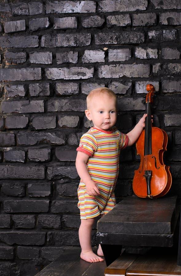 Ragazzino con il violino sul fondo del muro di mattoni fotografia stock libera da diritti
