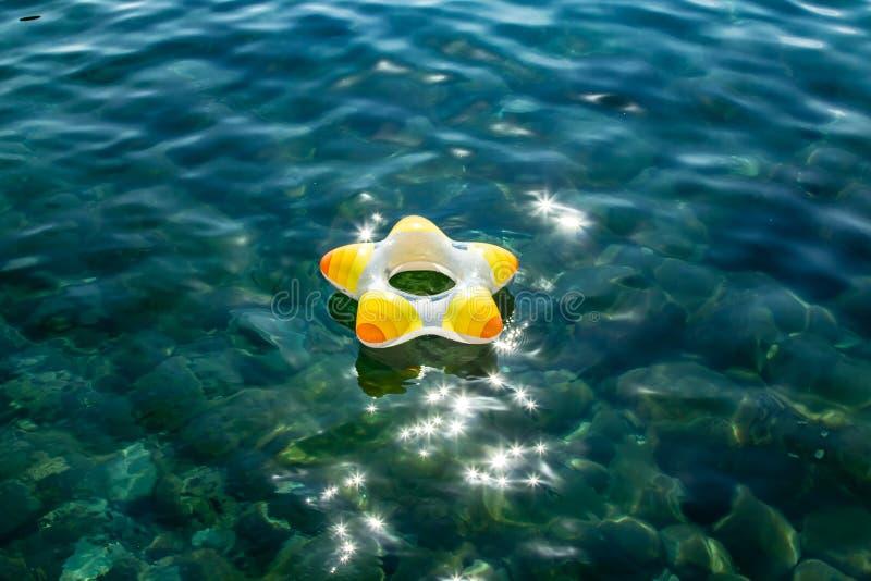 Ragazzino con l'anello di vita, anello di nuoto sull'acqua trasparente sul centro dell'immagine immagine stock libera da diritti