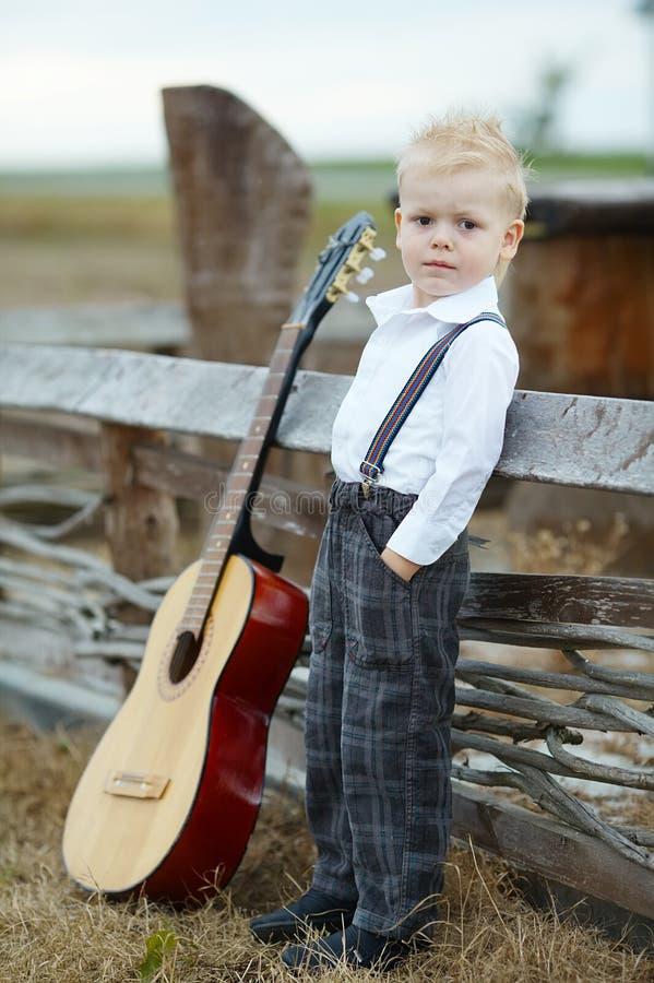 Ragazzino con la chitarra su posizione fotografia stock libera da diritti