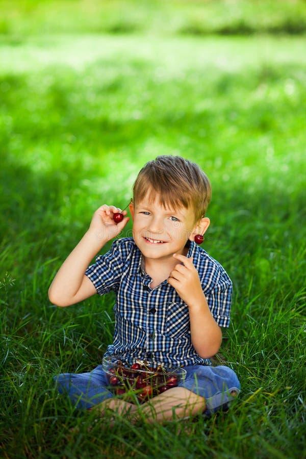 Ragazzino con la ciliegia su erba verde Giovani adulti fotografia stock libera da diritti
