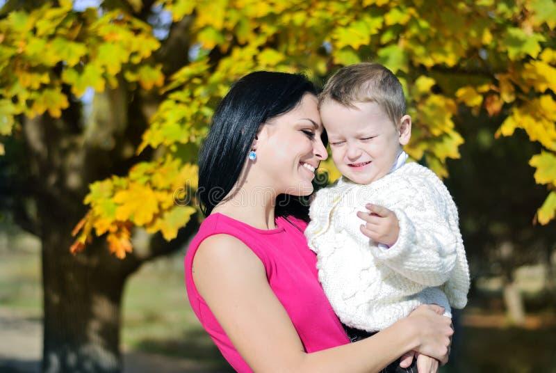 Ragazzino con sua madre nel parco di autunno immagine stock libera da diritti