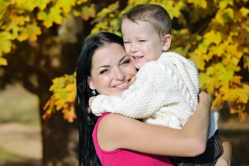 Ragazzino con sua madre nel parco di autunno fotografia stock