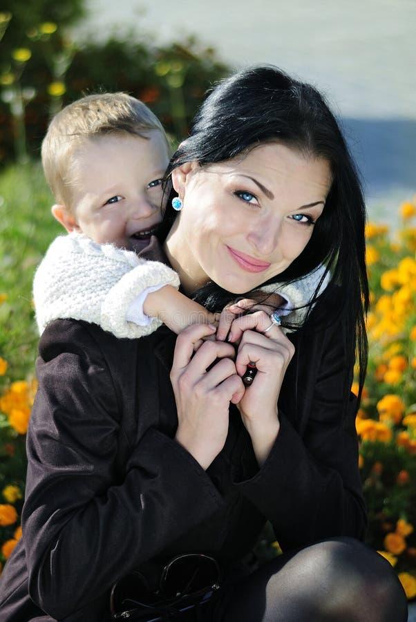 Ragazzino con sua madre nel parco di autunno immagini stock libere da diritti