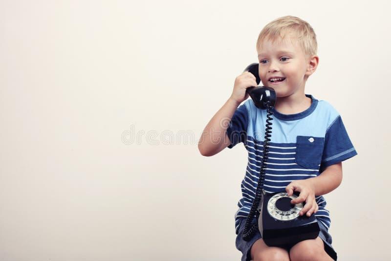 Ragazzino con un telefono metallico fotografia stock libera da diritti