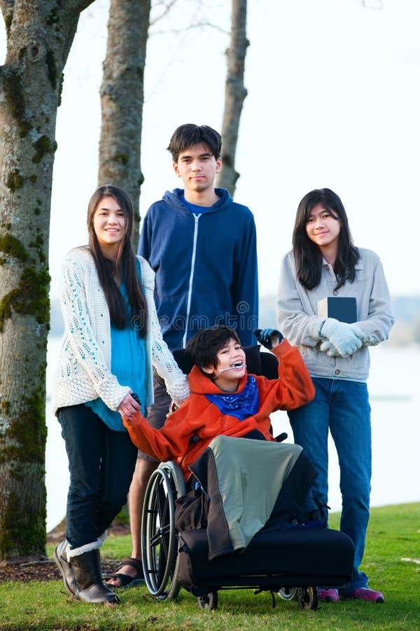 Ragazzino disabile in sedia a rotelle circondata dal fratello e dal sist immagini stock libere da diritti